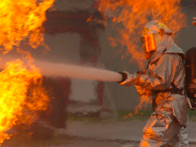 Firefighter extinguishing a fire in Australia for fire damage cleaning