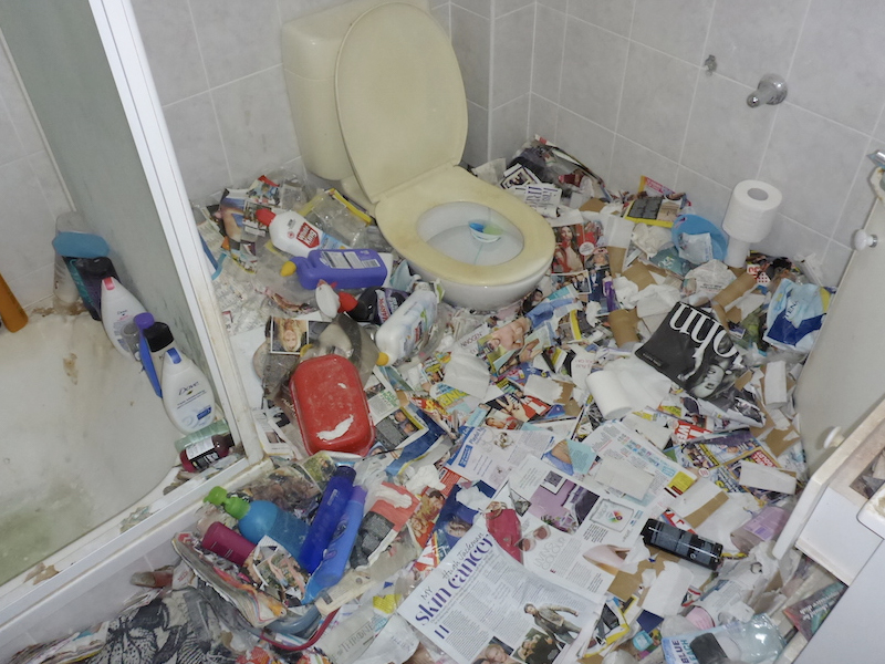 Hoarding home with rubbish in a bathroom